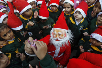 A student in a Santa Claus costume distributes sweets amongst school children during Christmas celebrations in Chandigarh