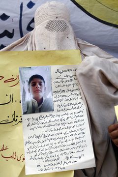 A woman, whose 11-year-old son Furqan Fareed was kidnapped by criminals more than a month ago, holds a sign during a sit-in with her family in Peshawar