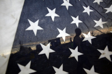 As photographed through an American flag, volunteers clear debris from a destroyed home in Joplin, Missouri