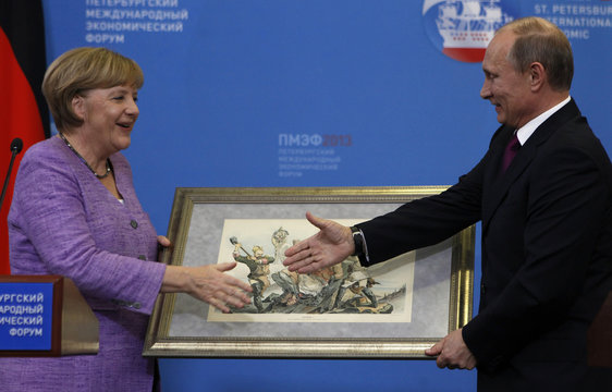 Russia's President Putin presents a historical lithograph to Germany's Chancellor Merkel during a news conference after their meeting at the St. Petersburg International Economic Forum in St. Petersburg