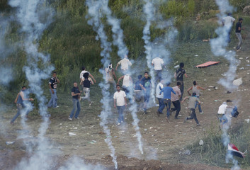 Protesters run away from tear gas fired by Israeli troops on the Syrian-Israeli border near Majdal Shams in the Golan Heights