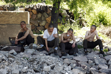 North Korean soldiers smoke on the banks of Yalu River, near Sinuiju
