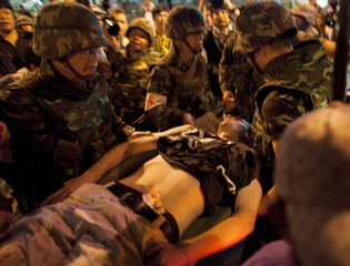 Thai army paramedics rush Ben Rown of Australia to an ambulance after he was injured from an explosion in Bangkok