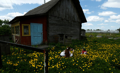 Woman takes photo of her daughter in flowers  after they took part in a ritual celebrating the pagan god Yurya and pray for plentiful future harvests in the village of Pogost