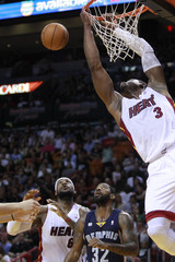 Miami Heat's Dwyane Wade misses this dunk against the Memphis Grizzlies as his teammate LeBron James and the Grizzlies' O.J. Mayo look on during the first half of their NBA basketball game in Miami