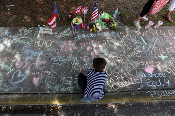 A child draws on the sidewalk in chalk at a makeshift memorial that is across the street from Pulse night club following last week's shooting in Orlando