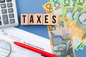 Taxes - Australia - wooden letters with tax form, magnifying glass, money and calculator