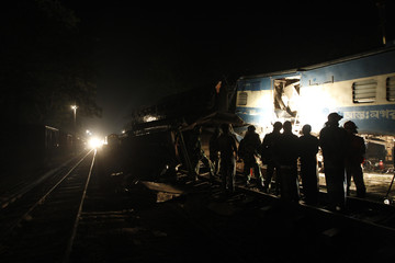 Rescue workers gather after two trains collided as another train approaches in Narsingdi