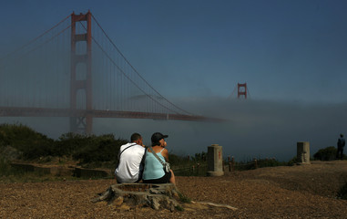 A couple looks out at the fog-shrouded Golden Gate Bridge in San Francisco
