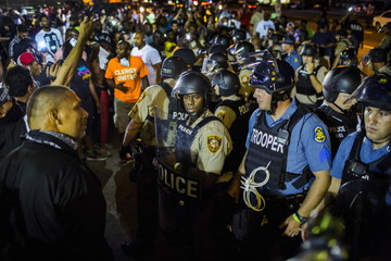 St Louis County police officers interact with anti-police demonstrators during protests in Ferguson, Missouri
