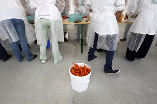 A container of carrots is seen near volunteers cutting vegetables to create the world's biggest vegetable salad during a Guinness World Record attempt in Pantelimo