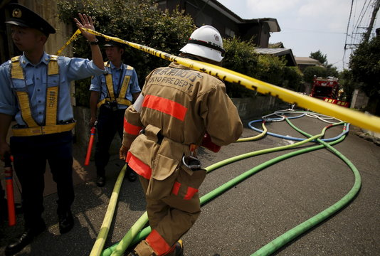 A firefighter rushes to the site where a light plane went down in a residential area and burst into flames, in Chofu, outskirt of Tokyo