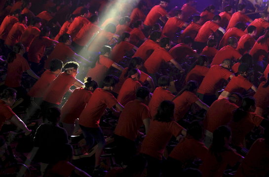 A participant is seen under a beam of light as hundreds of people ride indoor bicycles during a campaign to promote body-building exercises at a gymnasium in Kunming