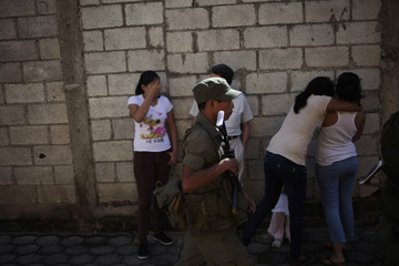 A soldier passes by people in the streets of Villanueva, in the outskirts of Guatemala City