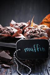 Chocolate dark muffin with a leaf of mint on a old black wooden table with  chocolate. Free text space, close up,  overhead shot with copy space.