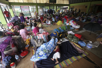 Families guard their belongings at a covered basketball court turned into an evacuation center in Marikina city