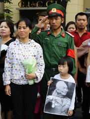 A girl holds a portrait of the late General Vo Nguyen Giap during his funeral on a street in Hanoi