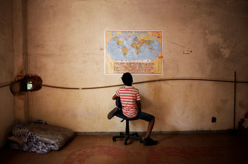 Wellington, a relative of a member of Brazil's Movimento dos Sem-Teto (Roofless Movement), looks at a world map in a vacant apartment during the occupation of an empty building in downtown Sao Paulo