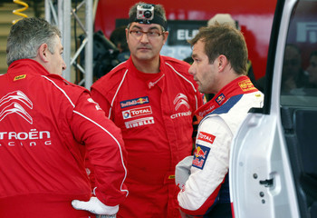 Citroen team driver Sebastien Loeb of France talks with mechanics during the shakedown stage of the WRC Rally of France in Strasbourg