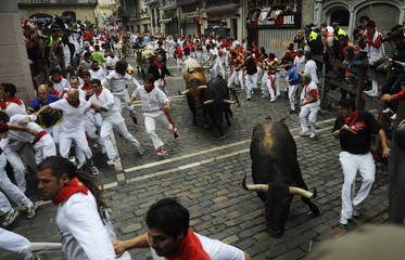 El Pilar fighting bulls sprint next to runners at Estafeta corner during the seventh running of the bulls at the San Fermin festival in Pamplona