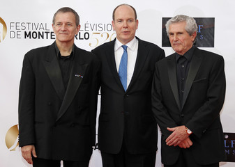 Monaco's Prince Albert II poses with actor Huster and director Lelouch during the opening ceremony of the 52nd Monte-Carlo Television Festival