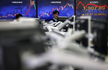 Currency dealers walks past an electronics board showing the KOSPI at a dealing room of a bank in Seoul