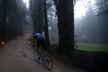 """A cyclist rides a vintage bicycle on gravel roads during the Strade Bianche section of the """"Eroica"""" cycling race for old bikes in Gaiole in Chianti"""
