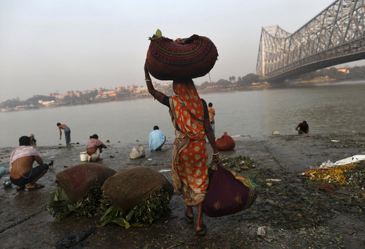 A woman carries sacks of leaves, which will be used to decorate flower bouquets, to be washed on the banks of the river Ganges in Kolkata