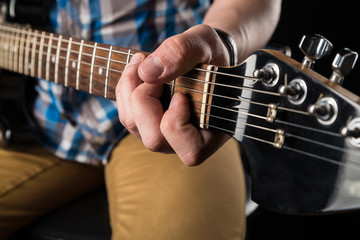 Music and art. Electric guitar in the hands of a guitarist, on a black isolated background. Playing guitar. Horizontal frame