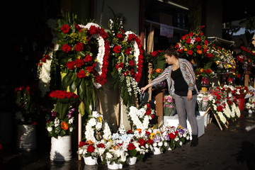 A woman waters flowers in downtown Los Angeles