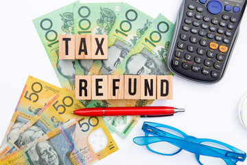 Tax Refund - Australia - wooden letters with eyeglasses, money and calculator