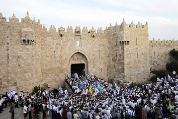 People wave Israeli flags during a parade marking Jerusalem Day, at Damascus Gate in Jerusalem's Old City