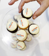 A guest at the public listing ceremony for Australian health insurer Medibank Private Ltd takes a cupcake featuring the company's logo in Sydney