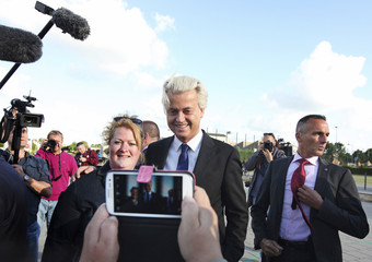Dutch Freedom Party leader Geert Wilders poses with a supporter during the Netherlands' general election in The Hague