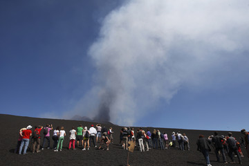 Tourists watch as Mount Etna spews volcanic ash during an eruption on the southern Italian island of Sicily