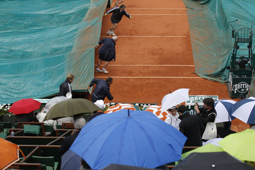 Grounds staff cover the court as rain stops the start of the men's singles semi-final match between Djokovic of Serbia and Federer of Switzerland during the French Open tennis tournament at the Roland Garros stadium in Paris