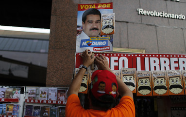 A street vendor arranges a picture of Venezuela's presidential candidate Maduro above a row of fake moustaches in Caracas