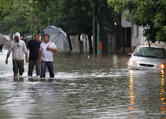 People wade through a flooded street after heavy rain in a Buenos Aires neighbourhood