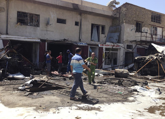 Residents inspect the site of a car bomb attack in the Hurriya District in Baghdad