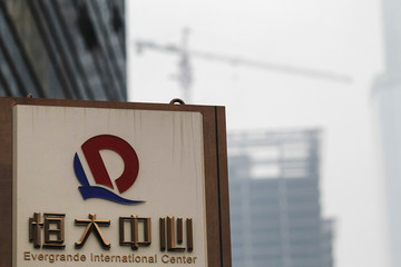 A logo of Evergrande Group is seen in front of a construction site in Guangzhou