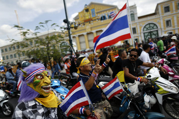 An anti-government protester, wearing a mask, gathers with other protesters outside the Defense Ministry in central Bangkok