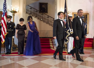 U.S. President Barack Obama and first lady Michelle Obama walk with Japan's Prime Minister Shinzo Abe and his wife Akie Abe at a State Dinner in their honor at the White House in Washington