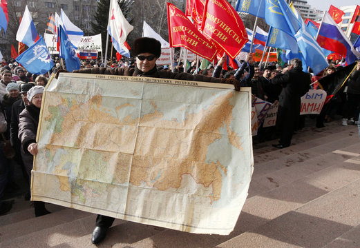 A man holds a map of the Soviet Union during a rally to support Crimean Russian speakers in Krasnoyarsk