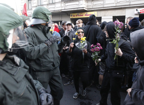 Left-wing protestors offer flowers to riot policemen during May Day demonstrations in Kreuzberg district of Berlin