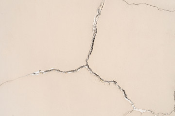 On the wall a large crack in the shape of a star on a beige plaster
