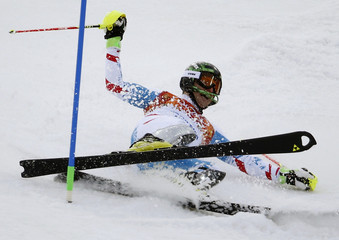 Austria's Herbst falls in the snow after crashing in the first run of the men's alpine skiing slalom event during the 2014 Sochi Winter Olympics at the Rosa Khutor Alpine Center