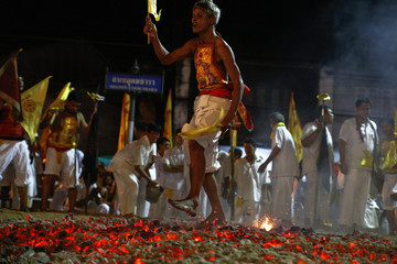 """A devotee of """"Chao Pho Kuan U Shrine"""" performs a fire-walking ceremony during celebrations for the vegetarian festival in Phang Nga"""