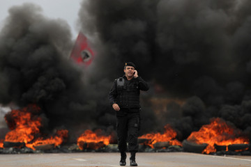 A police officer walks in front of burning tires placed on a highway by members of Movement of Landless Rural Workers who are protesting for change in the process of land reform in Brasilia