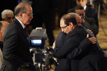 Libyan NTC Chairman Abdel Jalil hugs al-Alabbar, Chairman of the Electoral Commission National Congress, as Libya's PM El-Keib watches in Tripoli