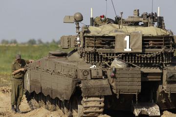 An Israeli soldier works on his tank near southern Gaza strip border near Kibbutz Kerem Shalom